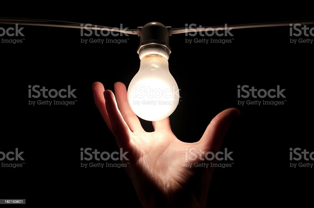 Hand reaching towards a light bulb royalty-free stock photo
