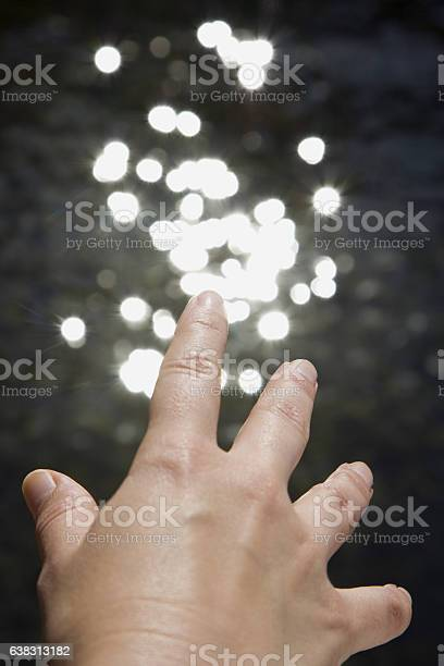Photo of Hand reaching towards reflections of sunlight in water