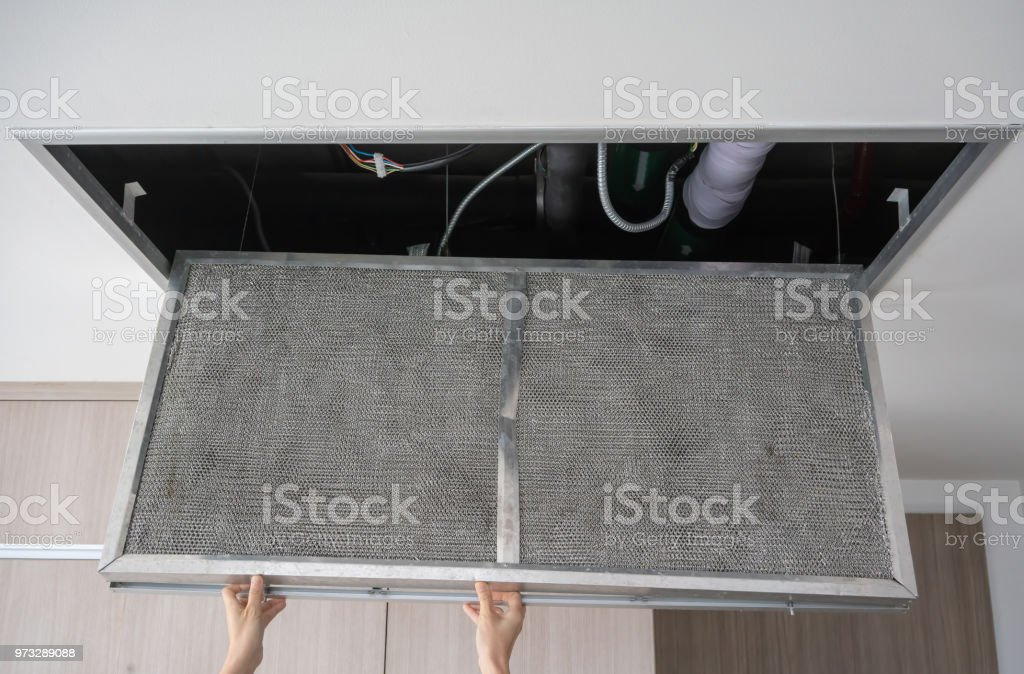 Hand reaching up to open filter holder for air conditioning filter in ceiling stock photo