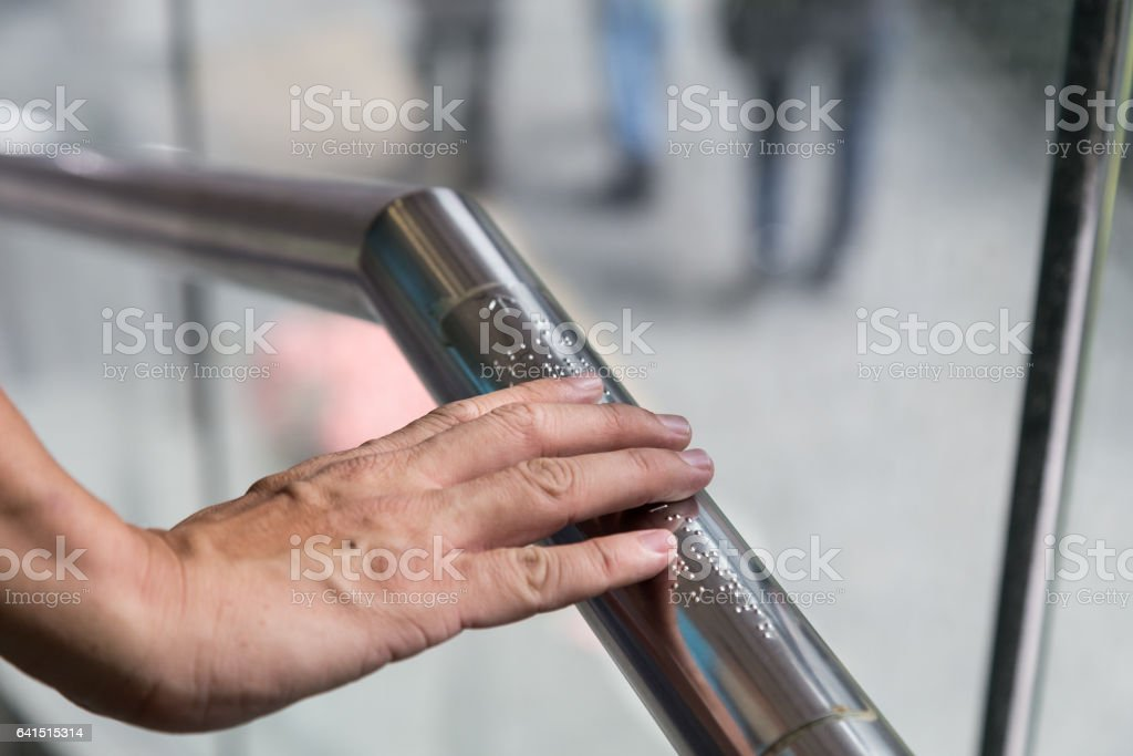 Hand reading Braille for the blind on public amenity railing stock photo