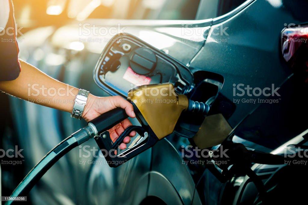 Ricarica a mano dell'auto con carburante alla stazione di rifornimento - Foto stock royalty-free di Adulto