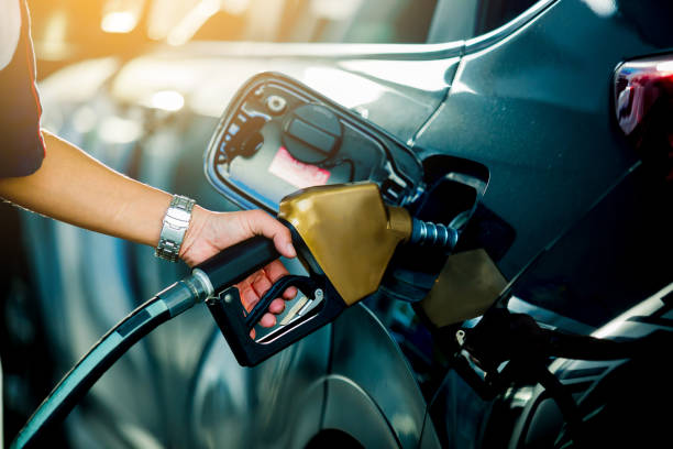 hand refilling the car with fuel at the refuel station - benzina foto e immagini stock