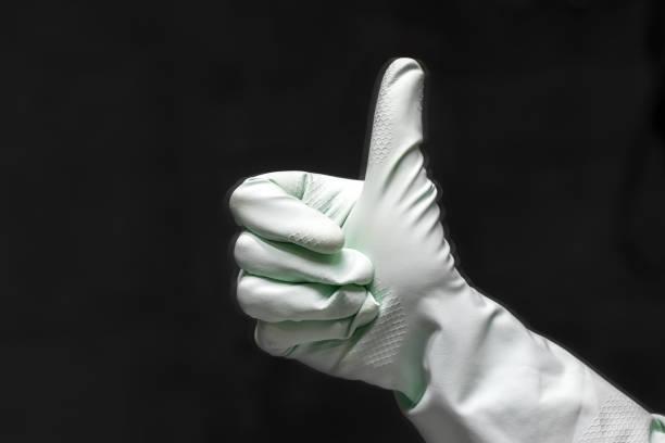 Un reflet de main dans un gant en caoutchouc vert menthe montre des pouces vers le haut dans une pièce foncée. Mise au point sélective. Vue de plan rapproché - Photo