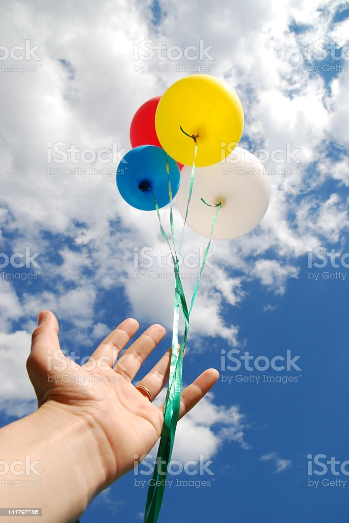 Hand releasing four colorful balloons into the sky stock photo