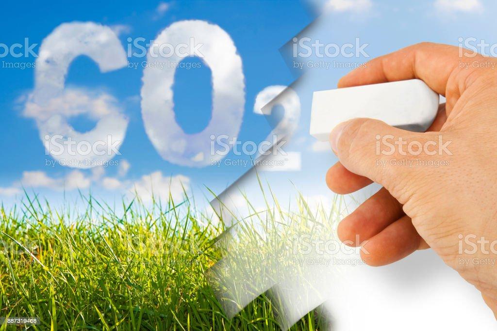 Mano quita el CO2 - imagen de concepto contra un pasto salvaje verde sobre fondo de cielo - foto de stock