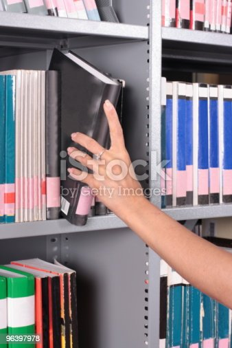 istock hand removing  a book from library shelf 96397978