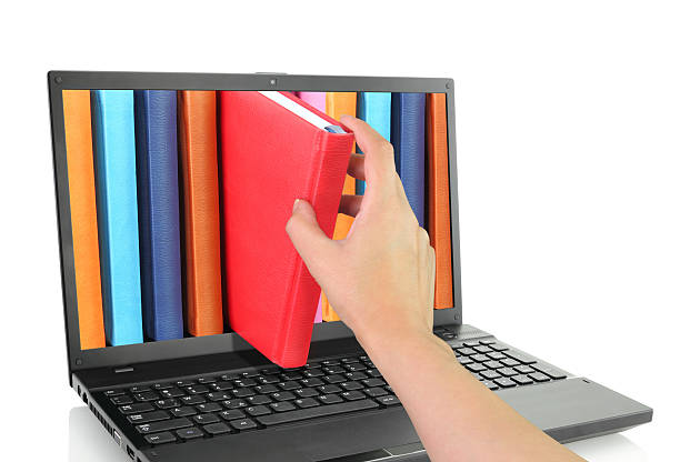Hand removing a book from notebook screen stock photo