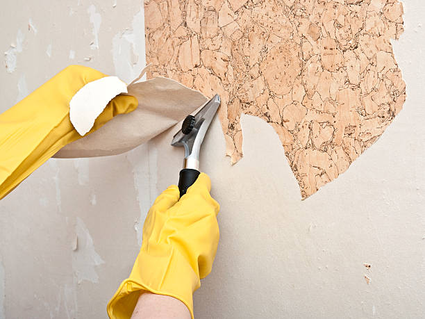 Hand removing wallpaper from wall stock photo
