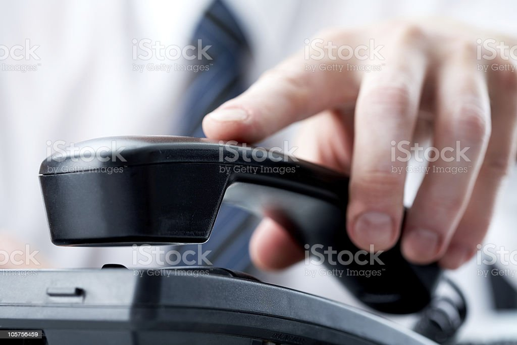 Hand replacing phone on the receiver stock photo
