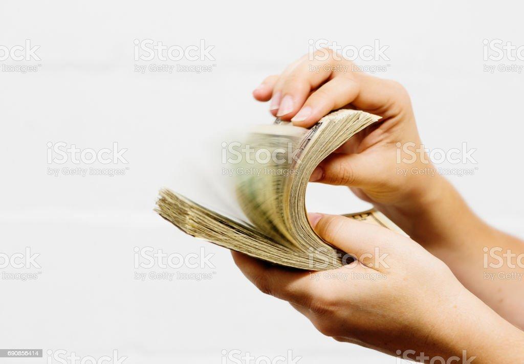 Hand riffles through bundle of US dollars, causing motion blur stock photo