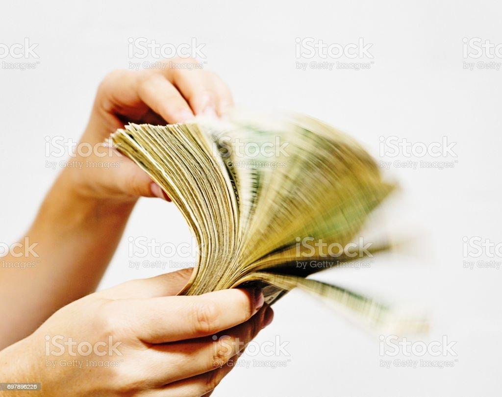 Hand riffles through wad of US dollars, causing motion blur stock photo