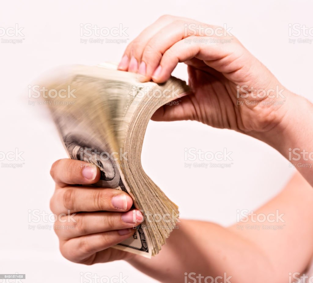 Hand riffling thick bundle of American banknotes stock photo