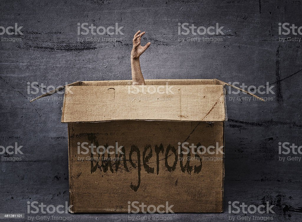 Hand rising out of box in dark and dirty environment stock photo