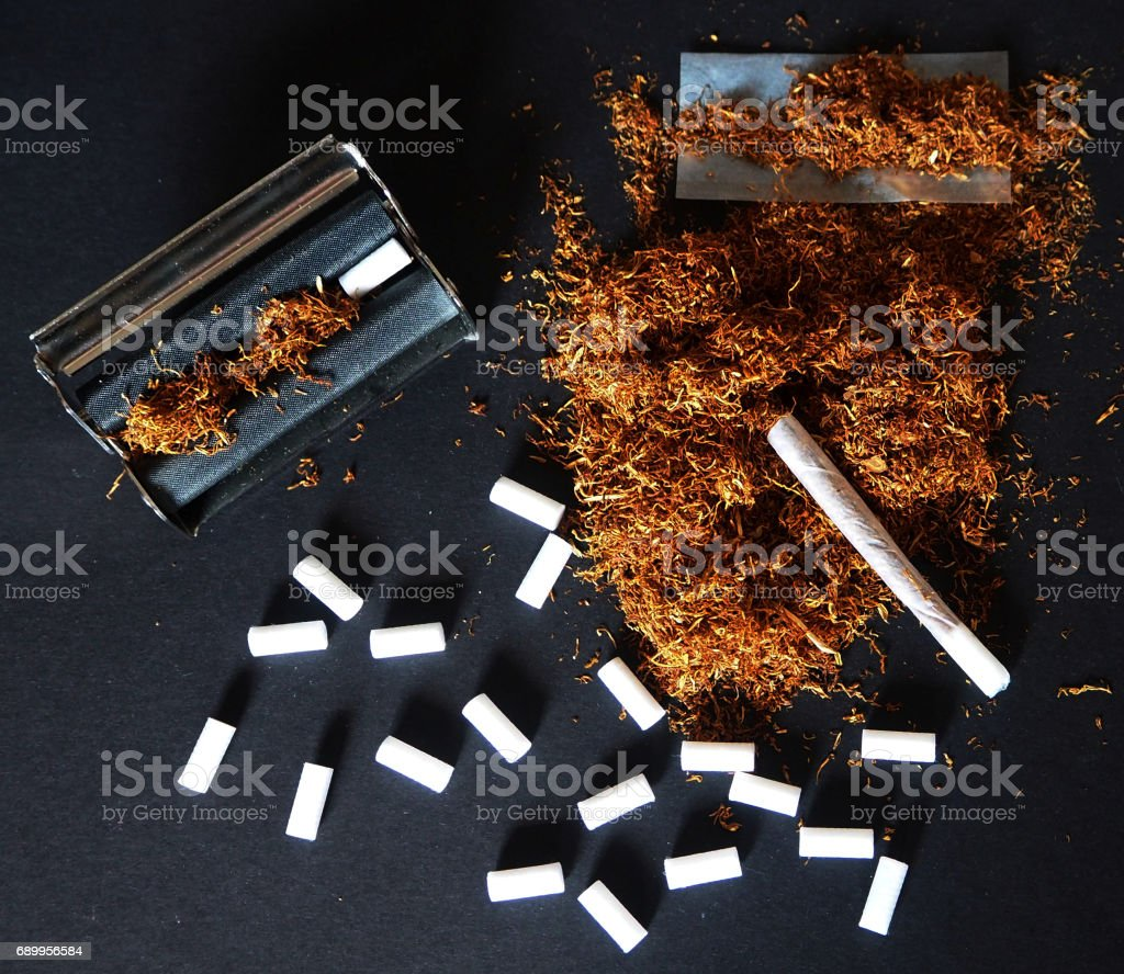 Hand rolled cigarette with tobacco stock photo