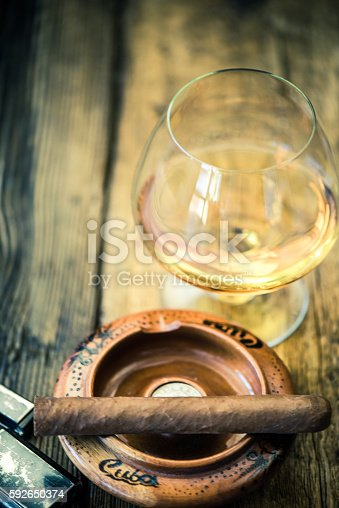 hand rolled cuban cigar and glass of rum or cognac