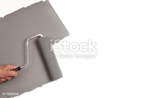 istock Hand rolling gray paint on white wall, copy space 511032010