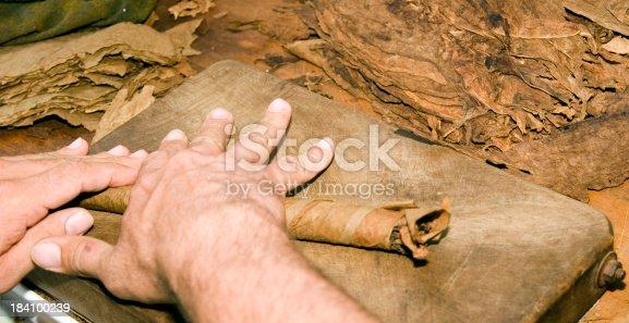 An artisan hand rolls a cigar.