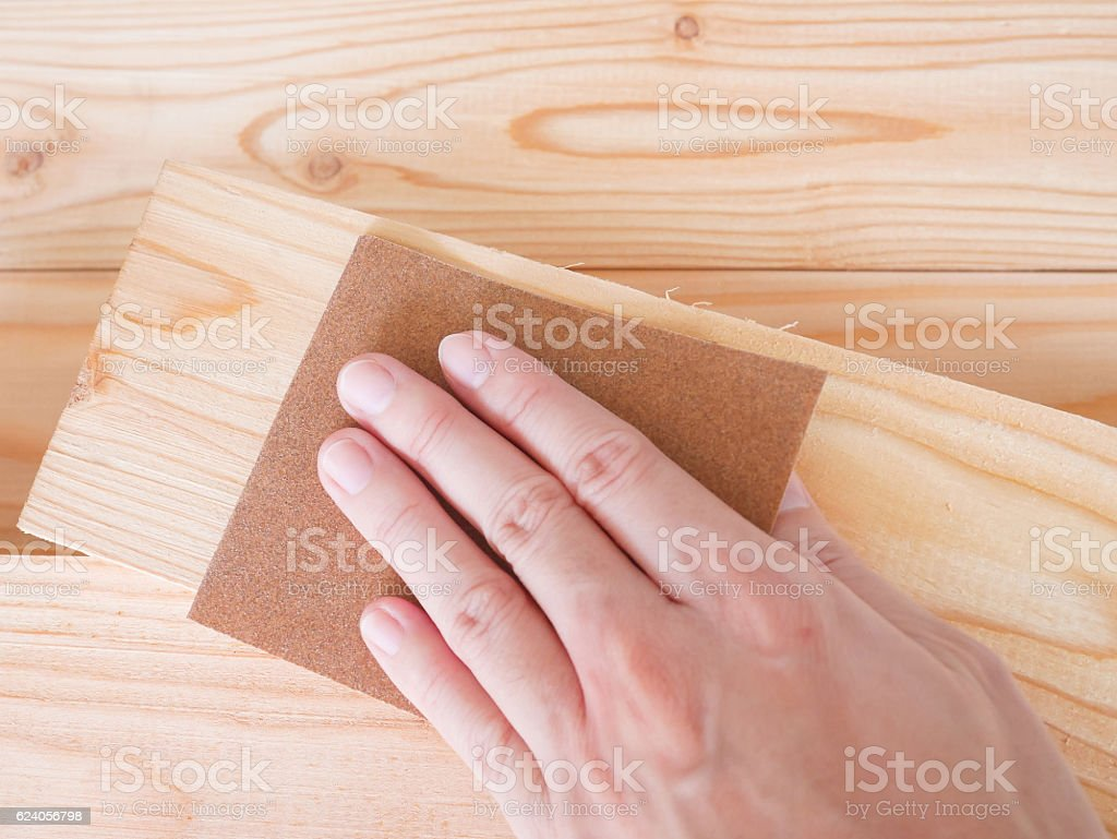 Hand sanding wooden pallet with sandpaper stock photo