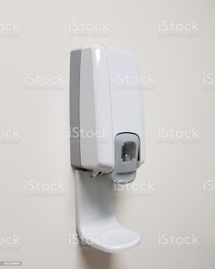 Hand sanitizer dispenser on a white wall stock photo