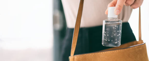 Hand sanitizer travel bottle woman carrying in purse COVID-19 prevention alcohol gel for cleaning hands while outside doing errands. Coronavirus virus pandemic banner panoramic header stock photo