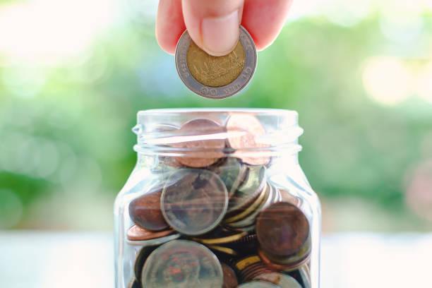 i̇ş ve finans konsepti için bulanık yeşil doğal arka plan cam kavanoza bir sikke tasarruf el - bearn stok fotoğraflar ve resimler