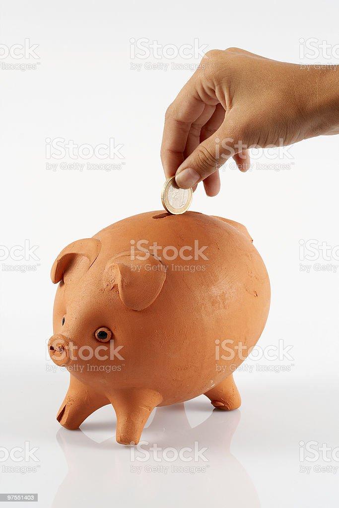 Hand saving money euro coin in piggybank royalty-free stock photo