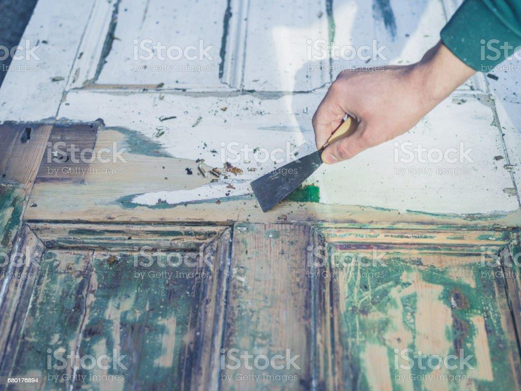 Hand scraping paint off door stock photo