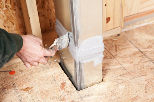 Hand Sealing House Air Duct Joint with Caulk
