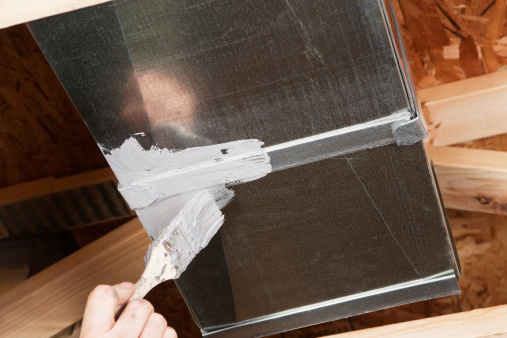 A male hand, holding a paintbrush, is spreading caulk over a house HVAC air duct seam. Caulking ducts prevents air-conditioned or heated air from escaping the duct and prevents ambient air from entering the system. This is a new practice in homebuilding to increase energy efficiency, eventually it may become standard or mandatory.