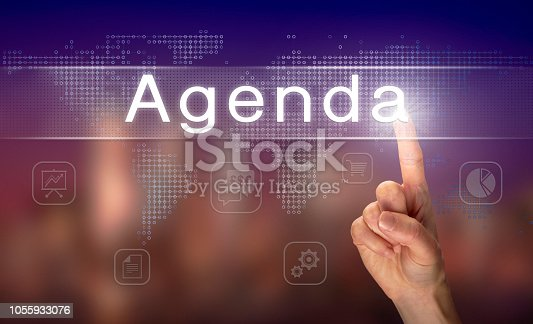 A hand selecting an Agenda business concept on a clear screen with a colorful blurred background.
