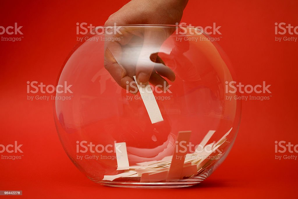 A hand selecting a paper ballot from a glass bowl on red royalty-free stock photo