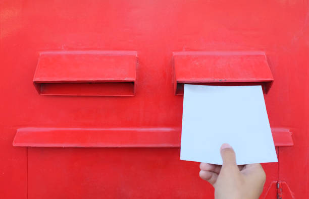 Hand sending a letter or postcard in a red Postbox. Hand sending a letter or postcard in a red Postbox. letterbox format stock pictures, royalty-free photos & images