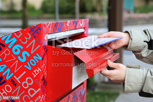 istock Hand sending tax report letter in red mail box 468773944