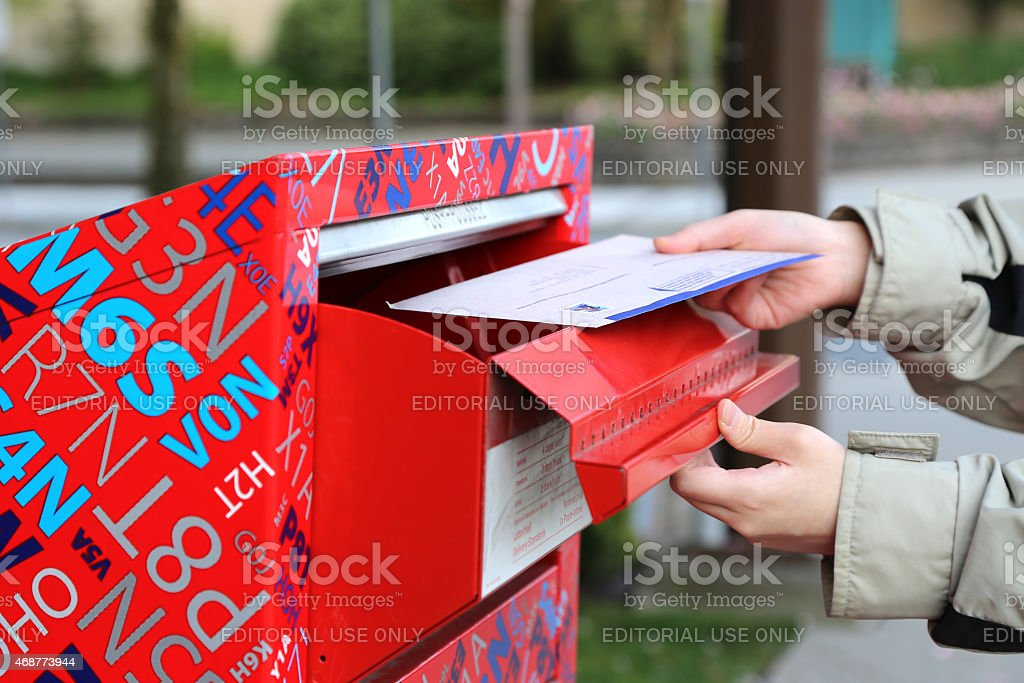 Hand sending tax report letter in red mail box stock photo