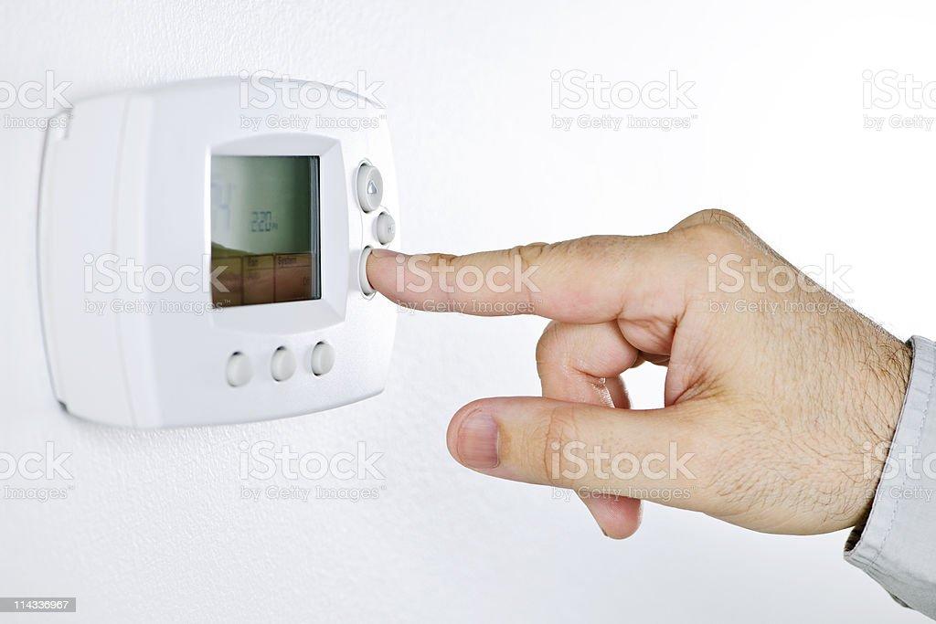 Hand setting digital thermostat stock photo