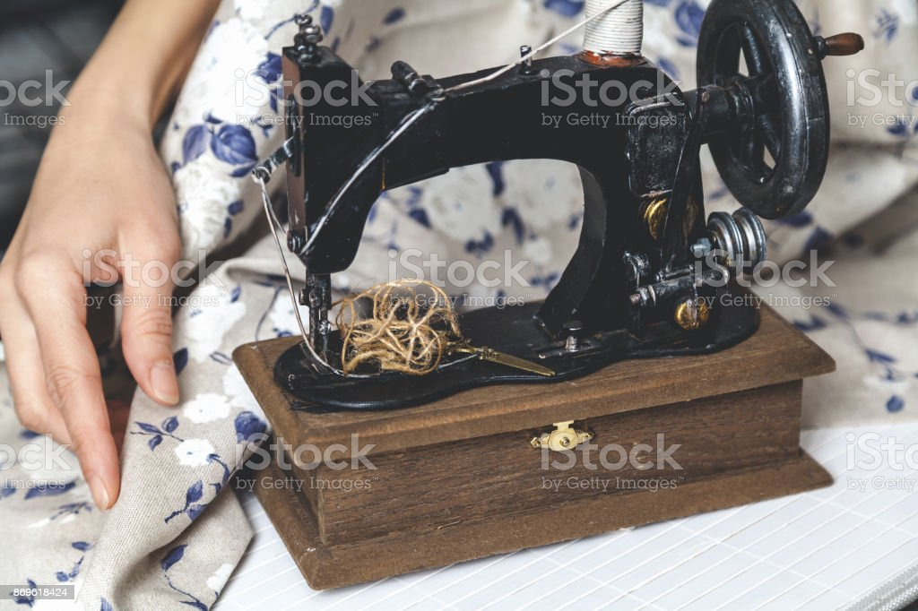 Hand sewing machine and hand of seamstress closeup stock photo