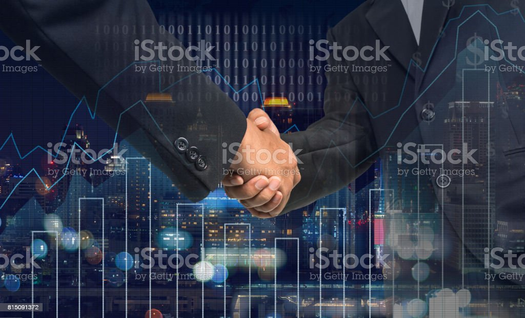 Hand shake between businessman on Trading graph on the cityscape at night and world map background,Business financial concept stock photo