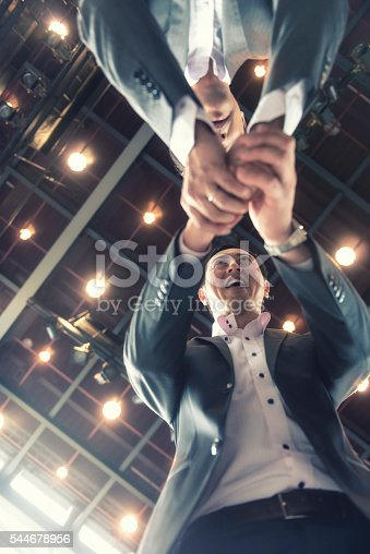 Hand shake of two Japanese businessman, view from below them. Theay have cheerful expression and they stand under high ceiling with lights. Japan.