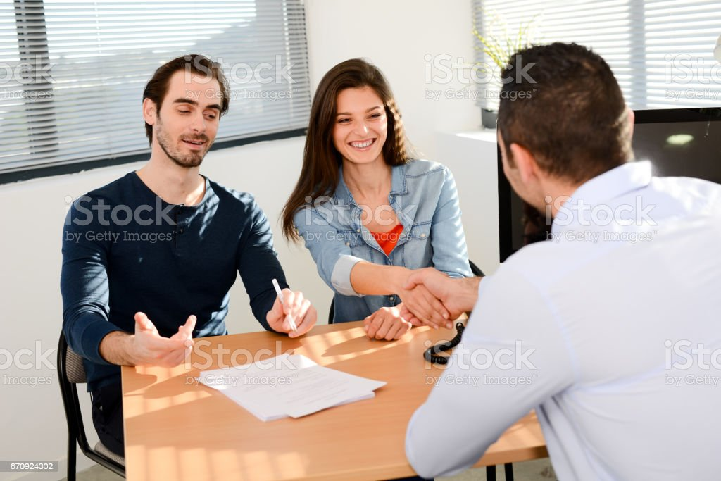 hand shaking and buying agreement contract signature between a young...