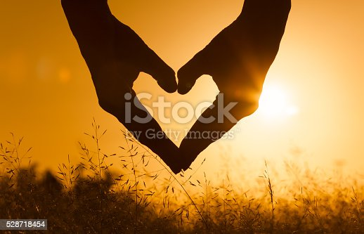 istock Hand shaped heart against a beautiful sunset 528718454