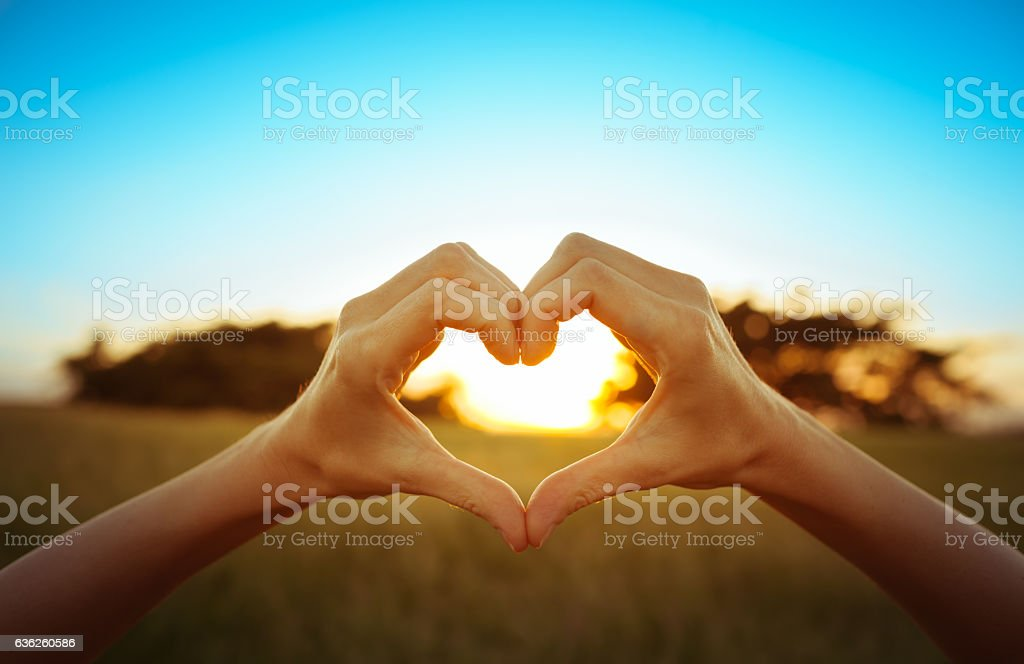 Hand shaped heart against beautiful sunset stock photo