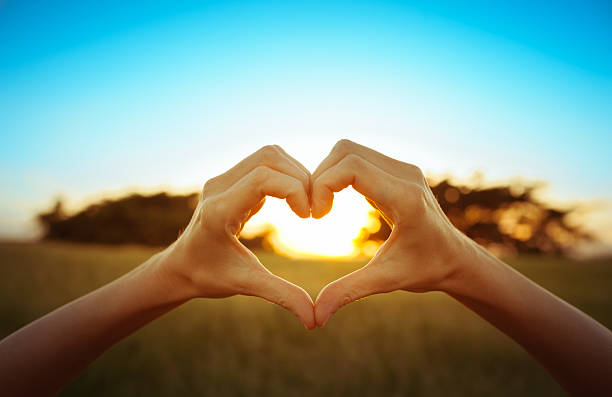 hand shaped heart against beautiful sunset - conceptual symbol stock pictures, royalty-free photos & images