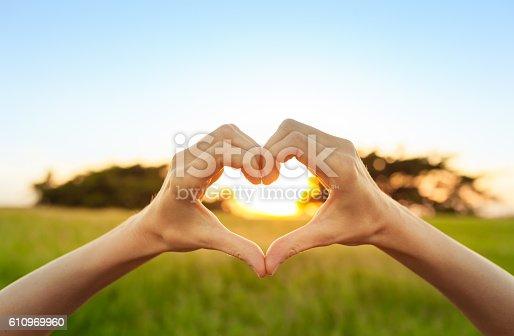 istock Hand shaped heart against sunset 610969960