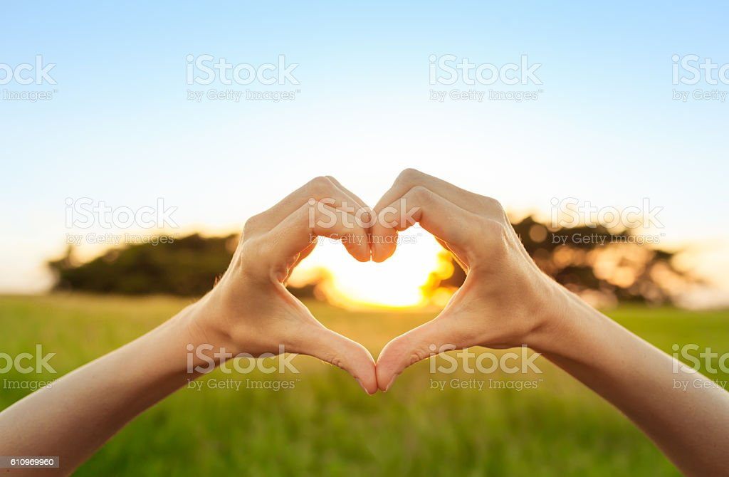 Hand shaped heart against sunset stock photo
