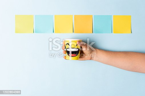Hand showing a happy emoticon paper cup on blue background with multicolor paper notes. Concept of social media, well-being, well done, feedback, employee recognition award.