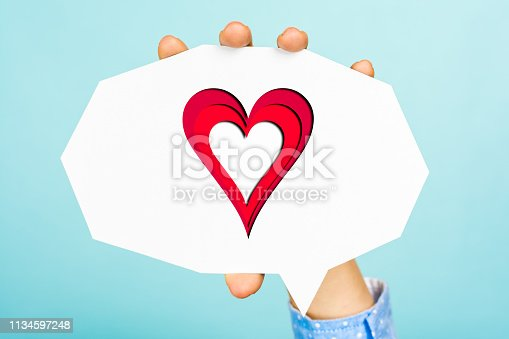 istock Hand showing a heart shape on empty white speech bubble with straight cutting shape, all this on blue background. 1134597248