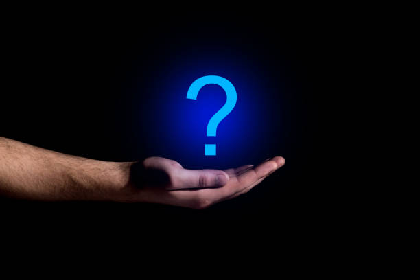 Hand showing a question mark in darkness stock photo