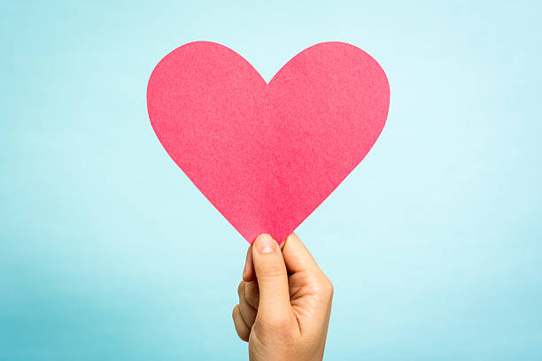 hand mit big red rosa herz liebe symbol blau hintergrund - herz zitate stock-fotos und bilder