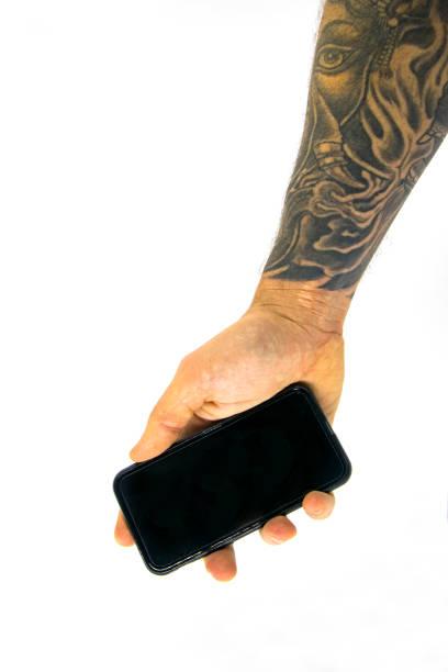 hand zeigt schwarz smartphone in weißen hintergrund isoliert - tatto vorlagen stock-fotos und bilder