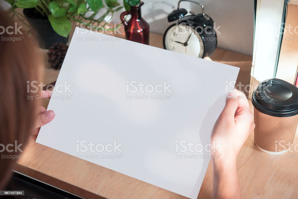 hand showing blank paper A4 flyer for mockup template design logo branding on wooden background. stock photo